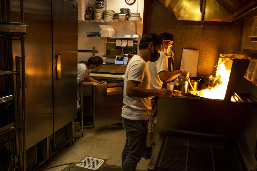 Prince Nuntanavooth works a fiery wok alongside his brother, Pacharej, in the back of J's Noodle and Star Thai Delivery on Federal Boulevard. Nov. 8, 2020.