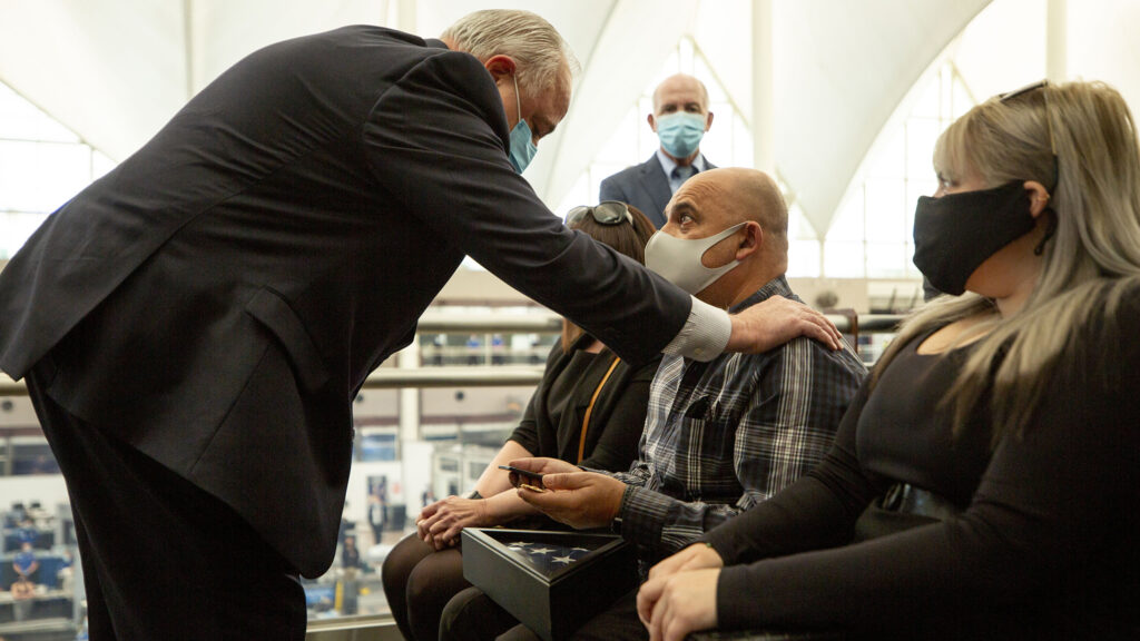 Colorado's Federal Security Director Larry Nau hands Oleg Faktorovich a medal during a memorial for his brother, Eduard, a TSA agent who died after contracting COVID-19. Nov, 21, 2020.