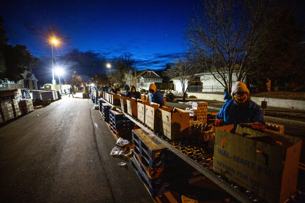Volunteers pack boxes with Thanksgiving meals before daybreak during the annual Denver Feed a Family event on Bruce Randolph Avenue. Nov. 21, 2020.