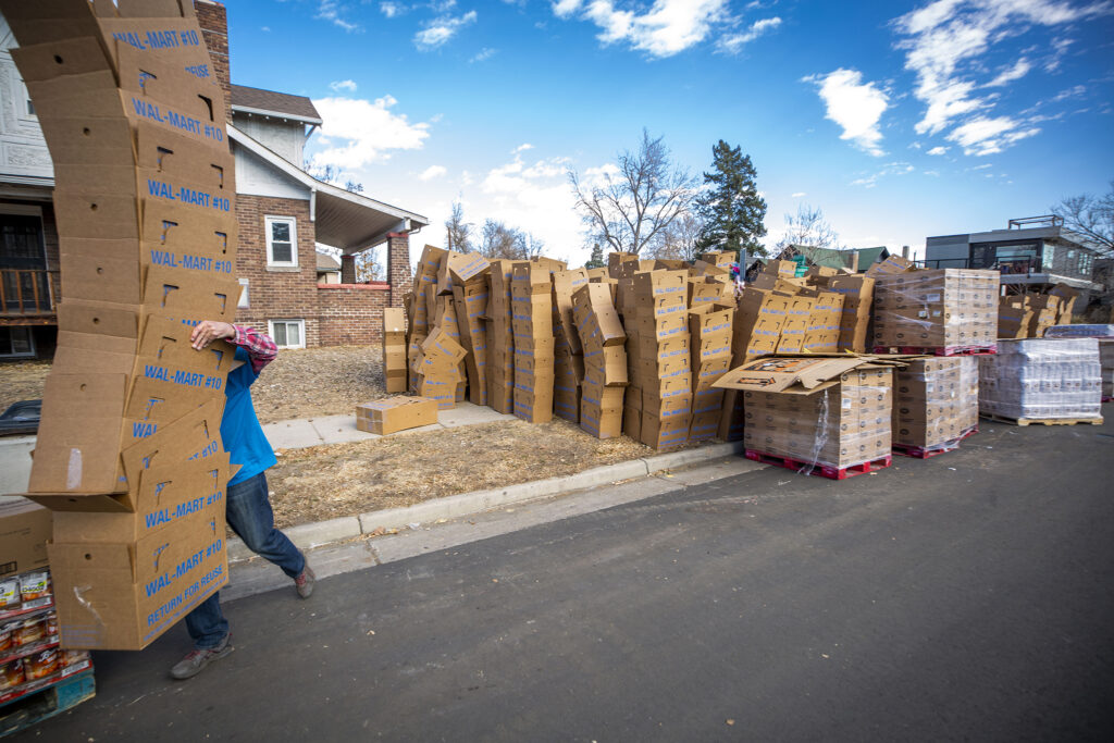 Donal Martin carries a large stack of boxes to be packed with turkies during the annual Denver Feed a Family event on Bruce Randolph Avenue. Nov. 21, 2020.