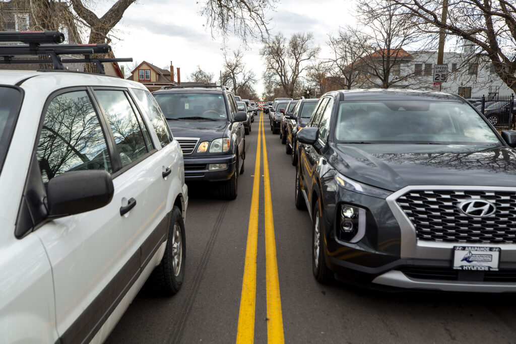 Cars line up to pick up Thanksgiving dinner boxes at the annual Denver Feed a Family event on Nov. 21, 2020. Most of these cars are here to pick up several boxes to deliver to families in need.