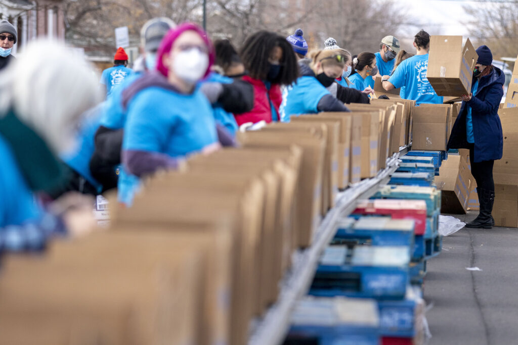 A long line of volunteers at work for the annual Denver Feed a Family event on Bruce Randolph Avenue in Cole. Nov. 21, 2020.