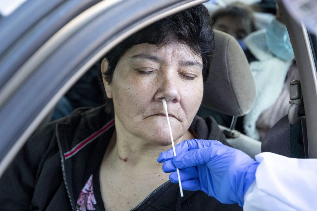 Nurse practitioner Karen Hoffman swabs Anita Wilson's nose for a COVID-19 rapid test outside Denver Indian Health and Family Services in Sun Valley. Nov. 24, 2020.
