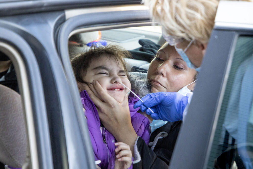 Loreen Wilson holds her daughter, Lilly, as nurse practitioner Karen Hoffman swabs her nose for a COVID-19 rapid test outside Denver Indian Health and Family Services in Sun Valley. Nov. 24, 2020.