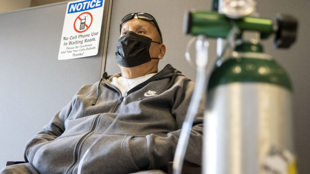 Loren Wilson sits in the waiting room at the Denver Indian Health and Family Services clinic in Sun Valley, breathing from an oxygen tank that he's been using to recover from COVID-19. Nov. 24, 2020.