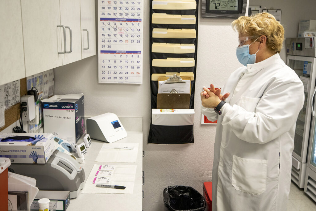 Nurse practitioner Karen Hoffman runs COVID-19 rapid tests in her lab at the Denver Indian Health and Family Services clinic in Sun Valley. Nov. 24, 2020.