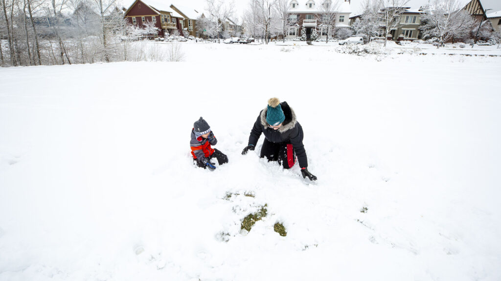Foster plays in the snow with his au pair, Ambar Tossolini, in GreenWay Park in the Central Park neighborhood. Nov, 24, 2020.