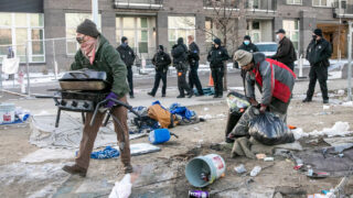 As Denver Police kept a small group of protesters at bay with fencing and, in a few cases, pepper ball rounds and mace, city crews began a sweep of a large homeless encampment at Arkins Court and 29th Avenue in Denver's RiNo district on Nov. 30, 2020. In this photo, volunteers are helping a man move his belongings as police stand nearby.