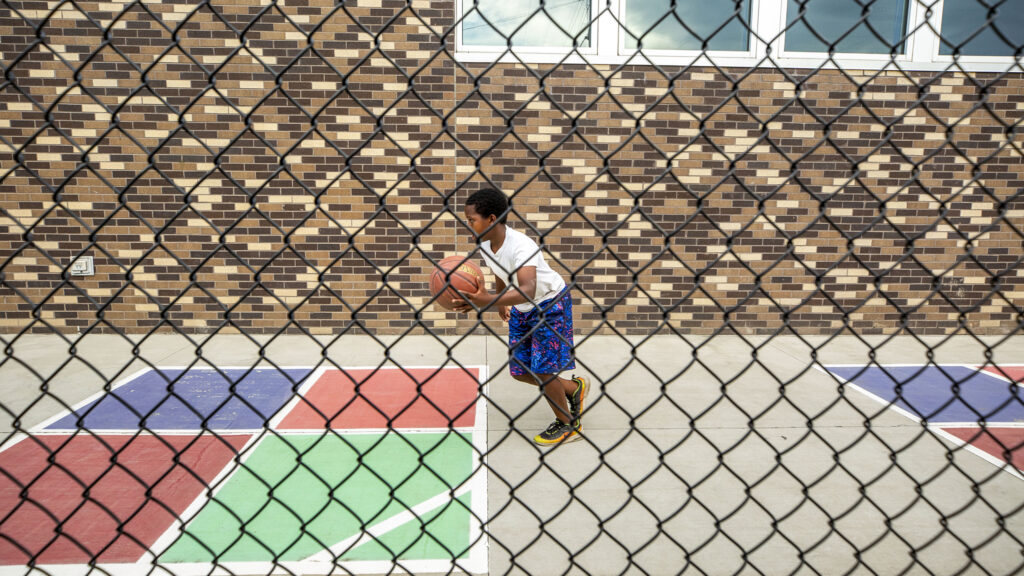 A kid plays basketball at the Dahlia Campus for Health and Well Being at the eastern end of Bruce Randolph Avenue. Sept. 11, 2020.
