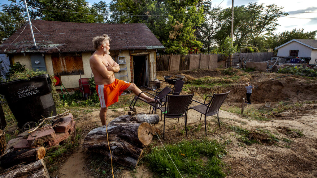 Nick Moses stands before the giant, ongoing, hand-dug pond pit in his back yard off Bruce Randolph Avenue as his son, Quentin, goes to work with a pickaxe. Sept. 11, 2020.