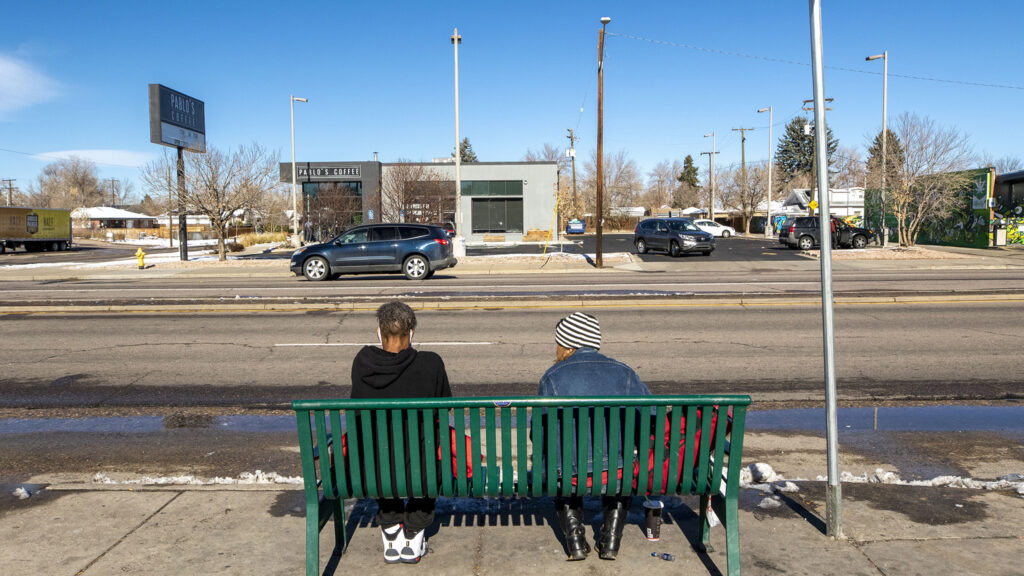 """Kristy Jo Gower, right, waits for a bus with someone she just met on East Colfax Avenue, Nov. 25, 2020. Gower said she'd spend a million dollars on helping people experiencing homelessness, like herself. """"They need help to stand up,"""" she said. """"They don't need a kick in the teeth."""""""