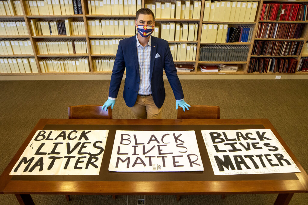 "History Colorado's Jason Hanson stands with ""Black Lives Matter"" signs collected during protests over the summer. Dec. 3, 2020."