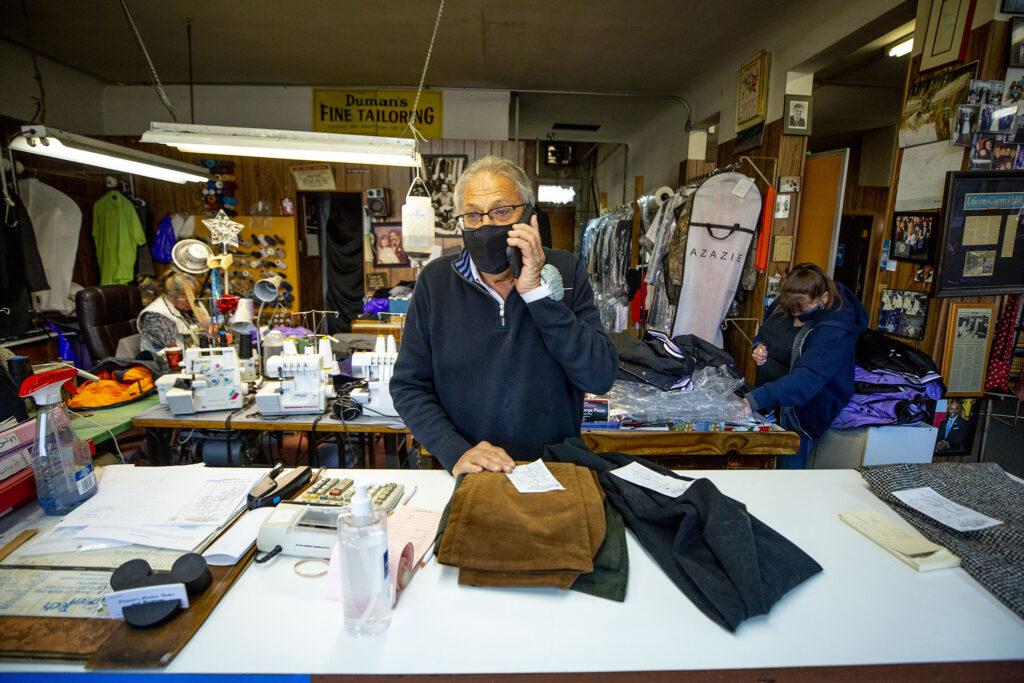 Steve Duman takes a call in his Colfax Avenue shop, Duman's Custom Tailor. Dec. 9, 2020.