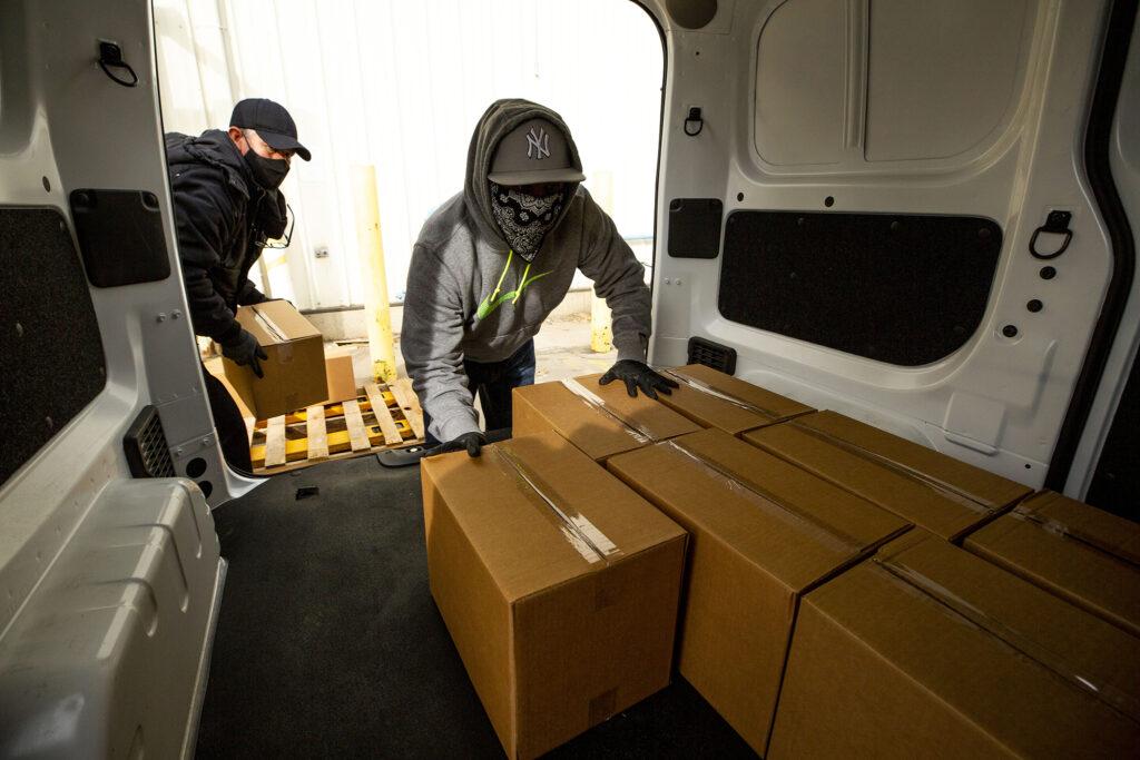 Fernando Hermosillo (left) and Felipe Lopez load Bondadosa food boxes into a van. Dec. 10, 2020.