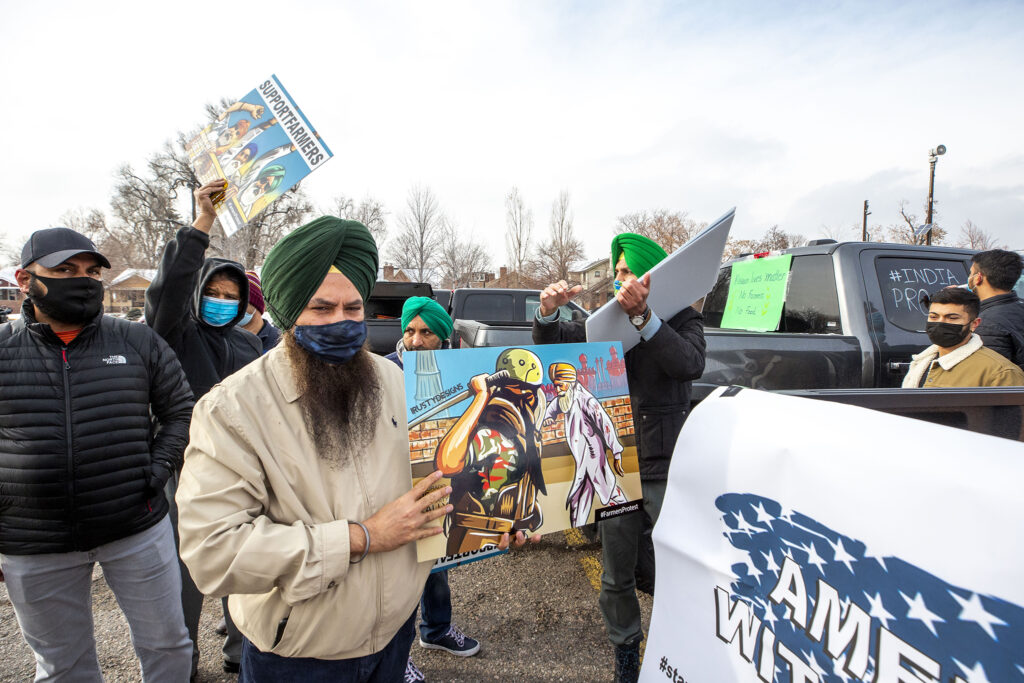 Jessie Singh holds a protest sign in South High School's parking lot during a rally in solidarity with massive demonstrations in India. Dec. 12, 2020.