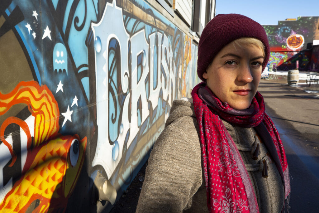 """Jessica Vaughan stands next to a """"CRUSH"""" mural off Walnut Street in the RiNo stretch of Five Points."""
