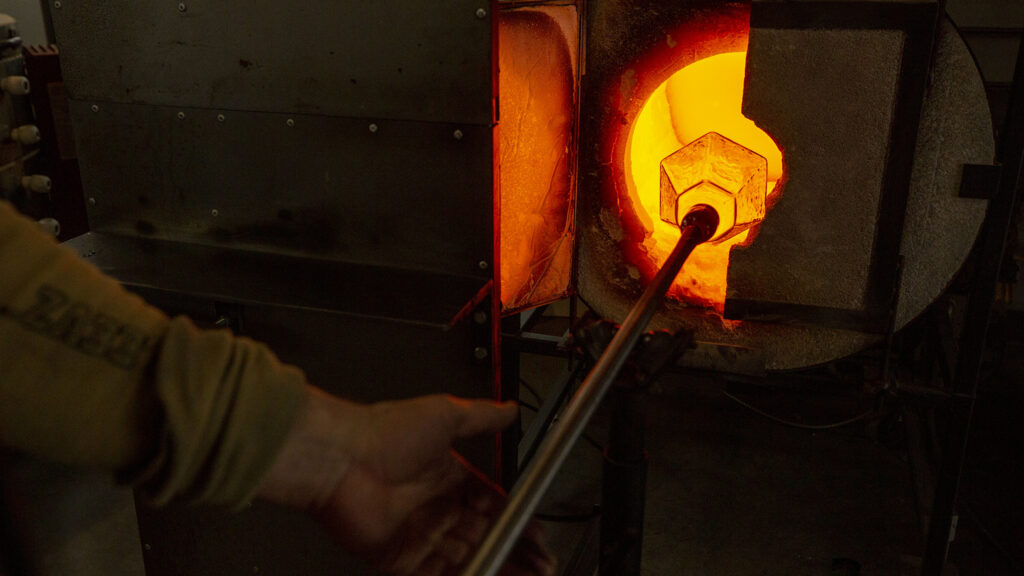 Nate Steinbrink pulls an in-progress light fixture out of a glowing kiln inside his Flux Studio workshop at Bruce Randolph Avenue and Elizbeth Street. Dec. 14, 2020.