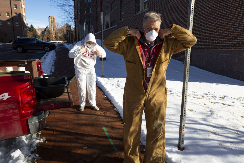 Work-study student Vander Georgeff (left) and Professor Keith Miller zip on work suits as they prepare to take wastewater samples outside of the University of Denver's Nelson Hall. Dec. 16, 2020.