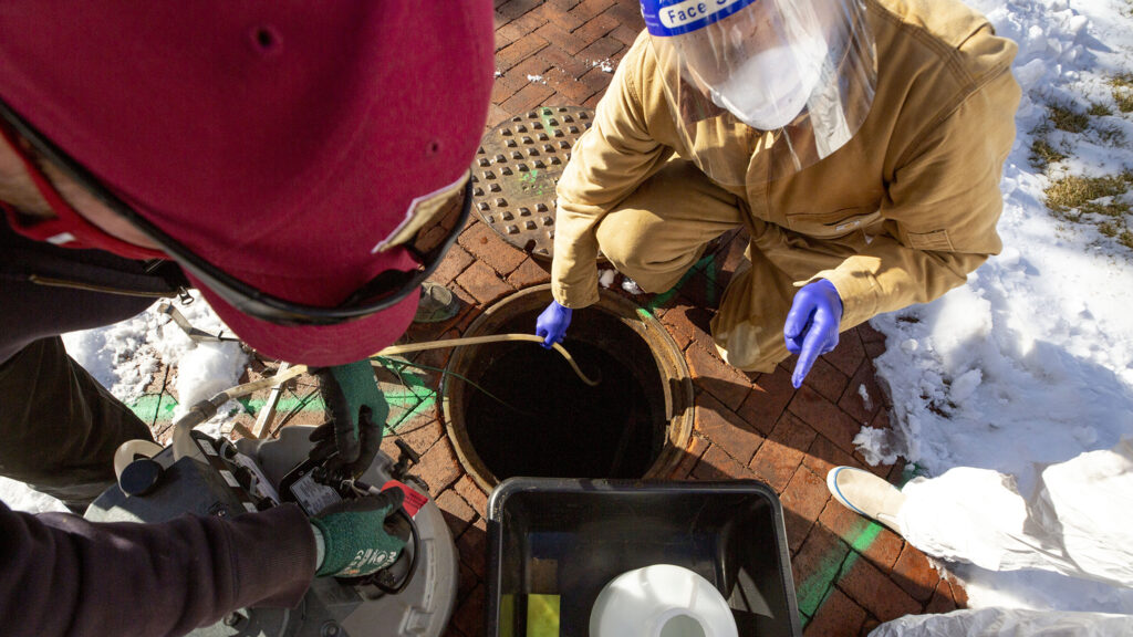 Shawn Martin (left to right), Professor Keith Miller and student Vander Georgeff remove a wastewater sampler from a manhole outside of the University of Denver's Nelson Hall. Dec. 16, 2020.