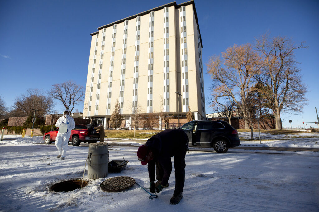 Shawn Martin (right to left), Professor Keith Miller and student Vander Georgeff remove a wastewater sampler from a manhole outside of the University of Denver's Nelson Hall. Dec. 16, 2020.