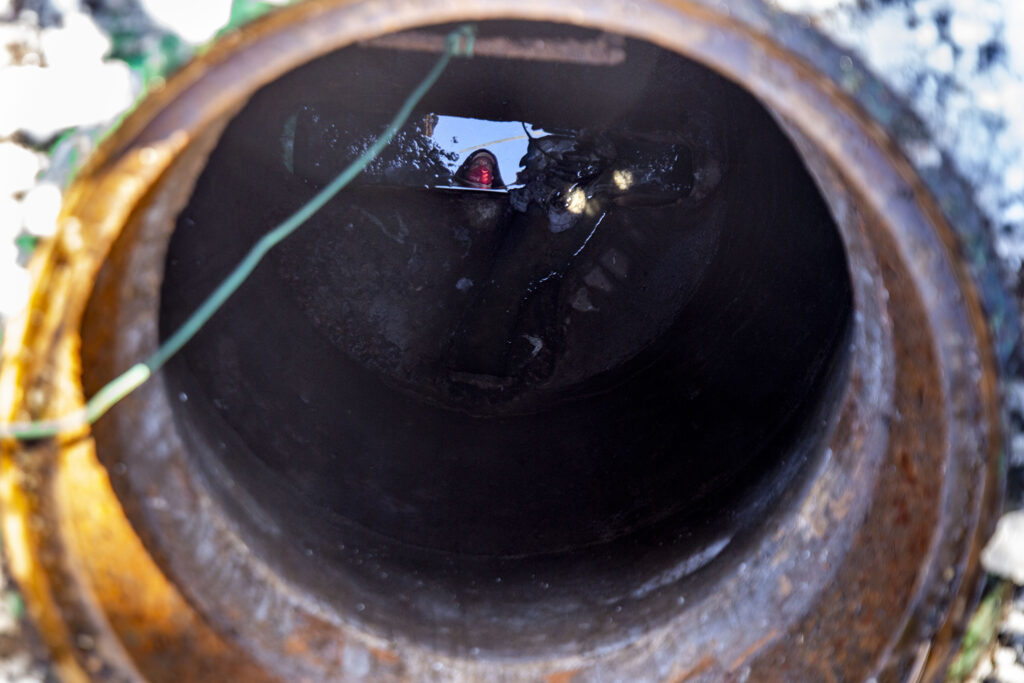 University of Denver plumbing shop worker Shawn Martin peers into a manhole outside of the Centennial Towers dormitory. Dec. 16, 2020.