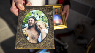 Stacy Neill holds a photo of her and her late partner, Todd Ham, in front of The Fourth Quarter apartments in Whittier. Dec. 17, 2020.