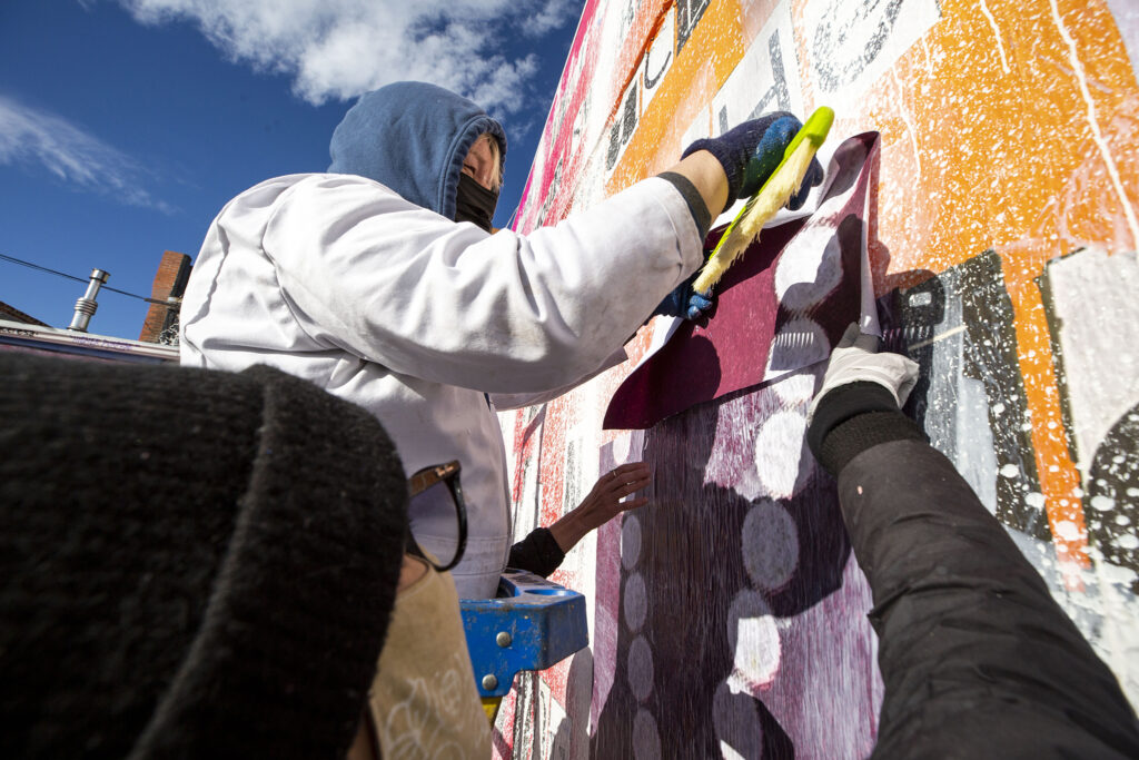 "Robyn Frances (left) and Koko Bayer plaster ""love"" over a mural to the women of Denver's art scene that was recently defaced off Larimer Street in Five Points' RiNo district. Dec. 19, 2020."