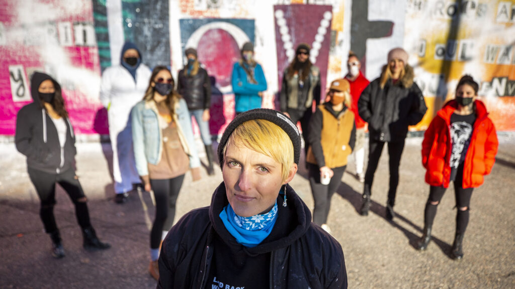 Surrounded by friends and supporters, Robyn Frances stands in front of a mural dedicated to the women of Denver's art scene, off Larimer Street in Five Points' RiNo district, that was recently defaced. Dec. 19, 2020.