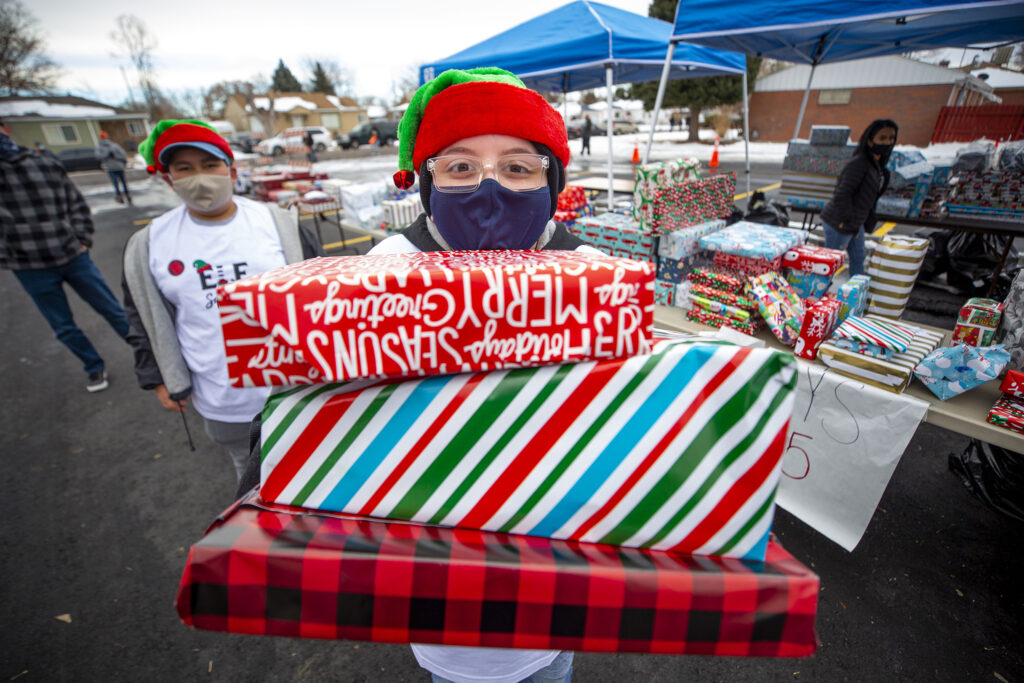 Andrew, 12, hands out free wrapped gifts during Victory Outreach Church's annual toy giveaway in Athmar Park. Dec. 19, 2020.