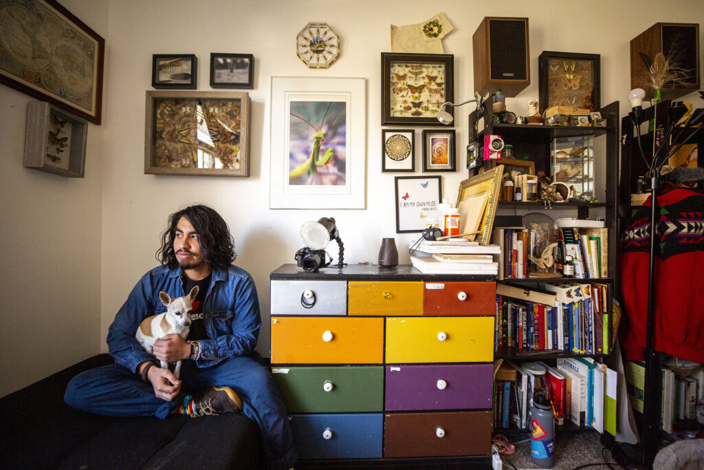 Efrain Leal Escalera and Bambi the dog in his room at home in Aurora. Dec. 26, 2020.