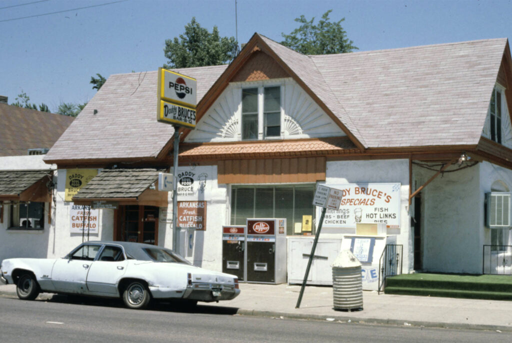 View of Daddy Bruce's BBQ in a modified queen Anne style house at 1629 East 34th Avenue, which is now Bruce Randolph Avenue. Circa 1980.