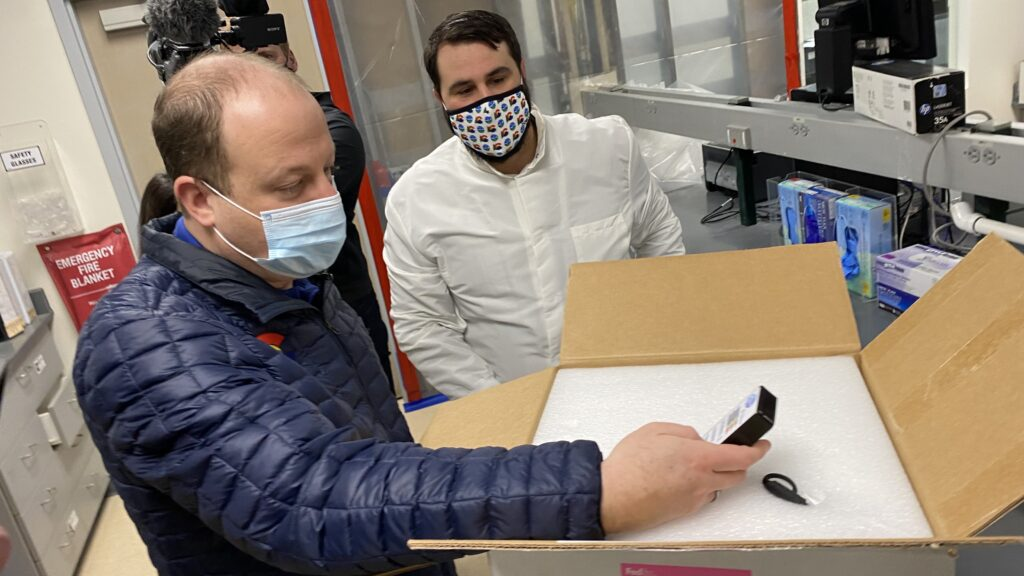 Gov. Jared Polis stands next to a box containing a COVID-19 vaccine on Monday, Dec. 14, at a state laboratory in Denver. (John Daley/CPR News)