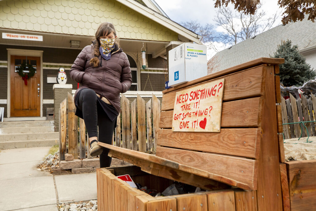 Maggie Thompson and the little free food pantry outside of her home in Clayton. Jan. 5, 2020.