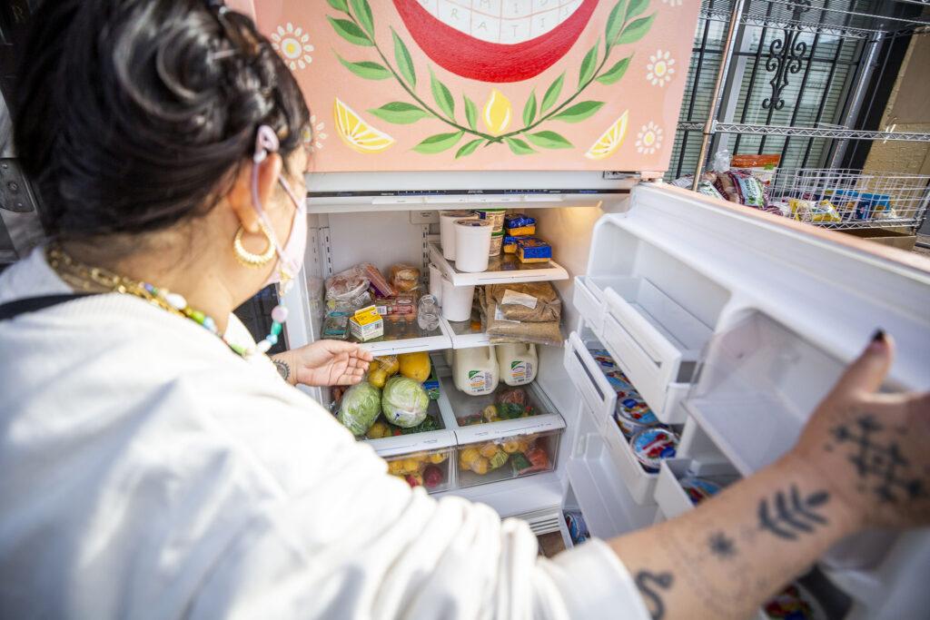 Tran Wills peers into the little free fridge outside of Base Coat, her salon, along Walnut Street. Jan. 5, 2020.