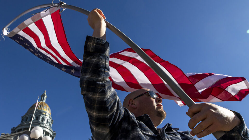 Ian Sylvester, of Hudson, Co., waves a huge flag during a rally in support of President Donald Trump in front of the Colorado State Capitol. Jan 6, 2021.
