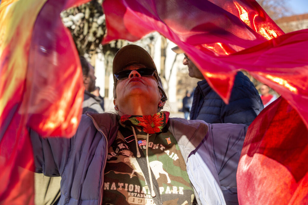 Yvonne Dawdy dances beneath two flying flags during a rally in support of President Donald Trump in front of the Colorado State Capitol. Jan 6, 2021.