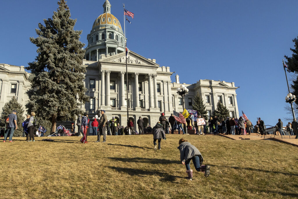 Kids play in the grass during a rally in support of President Donald Trump in front of the Colorado State Capitol. Jan 6, 2021.