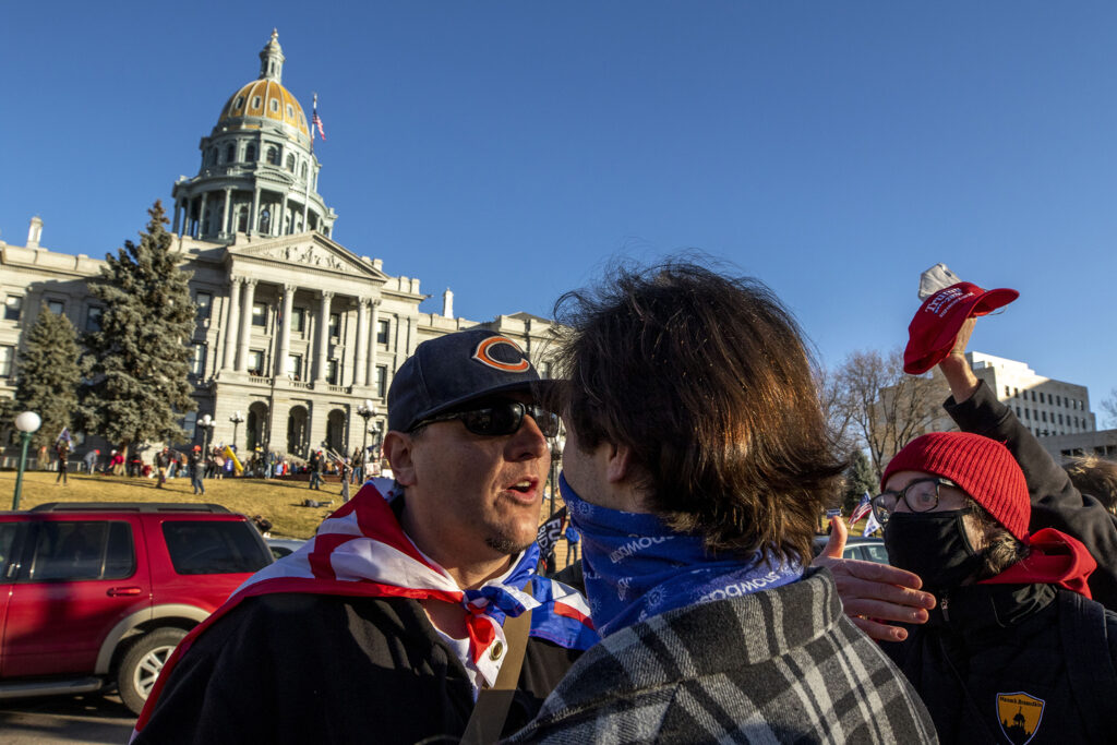 Men argue during a rally in support of President Donald Trump in front of the Colorado State Capitol. Jan 6, 2021.