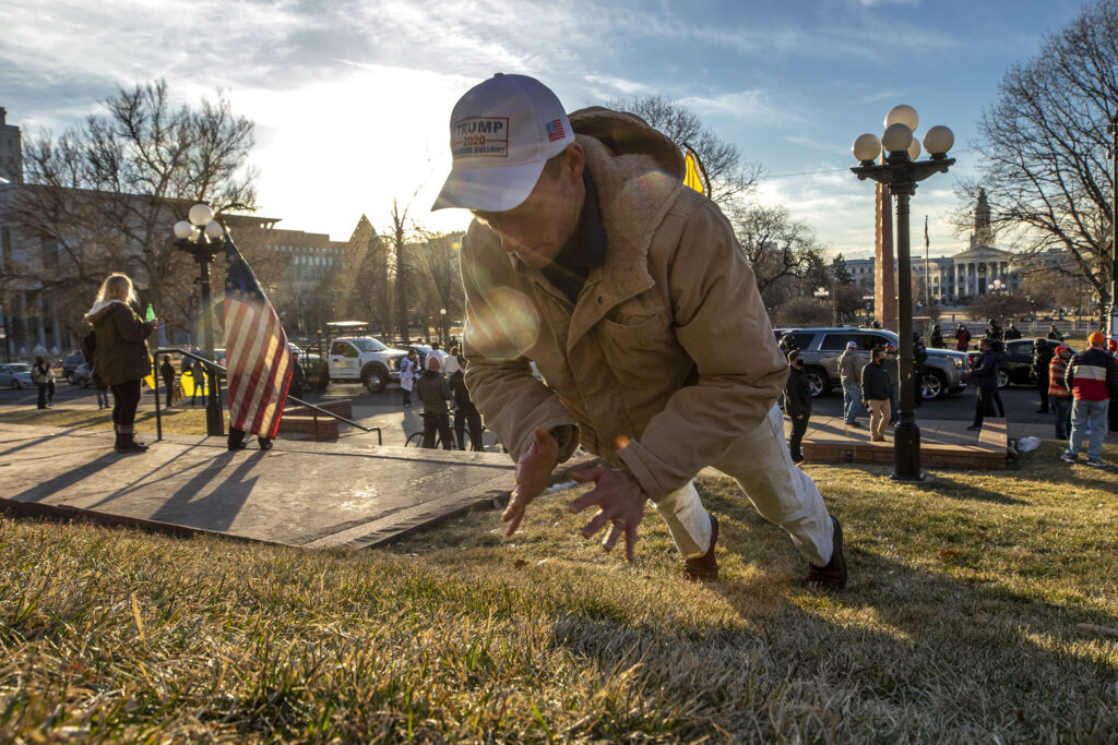 Connor Evans works out in the grass during a rally in support of President Donald Trump in front of the Colorado State Capitol. Jan 6, 2021.