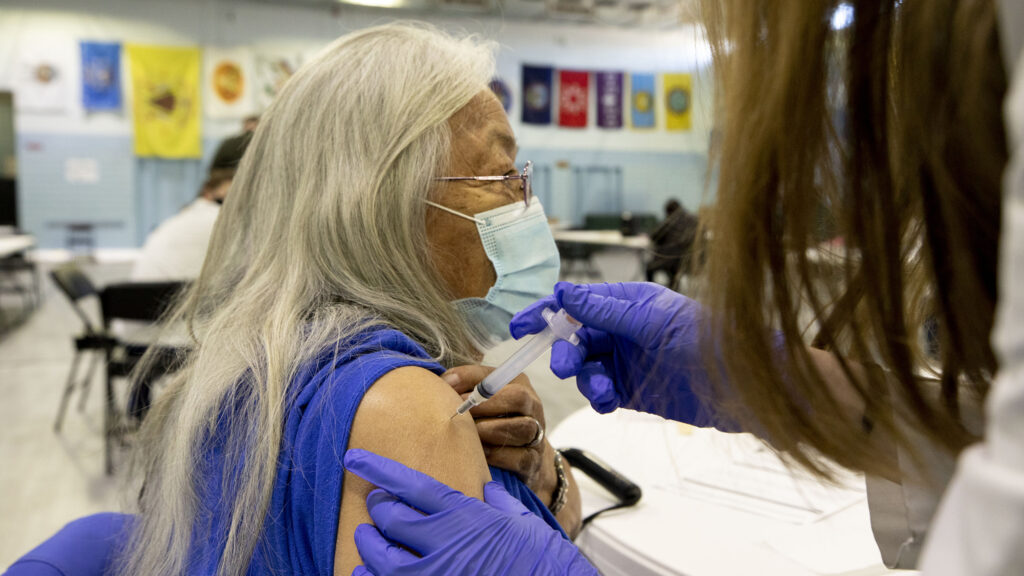 Gina Cammarata gets the first round of a Moderna COVID-19 vaccine at the Denver Indian Center, part of the second wave of prioritized shots in the city. Jan. 8, 2020.