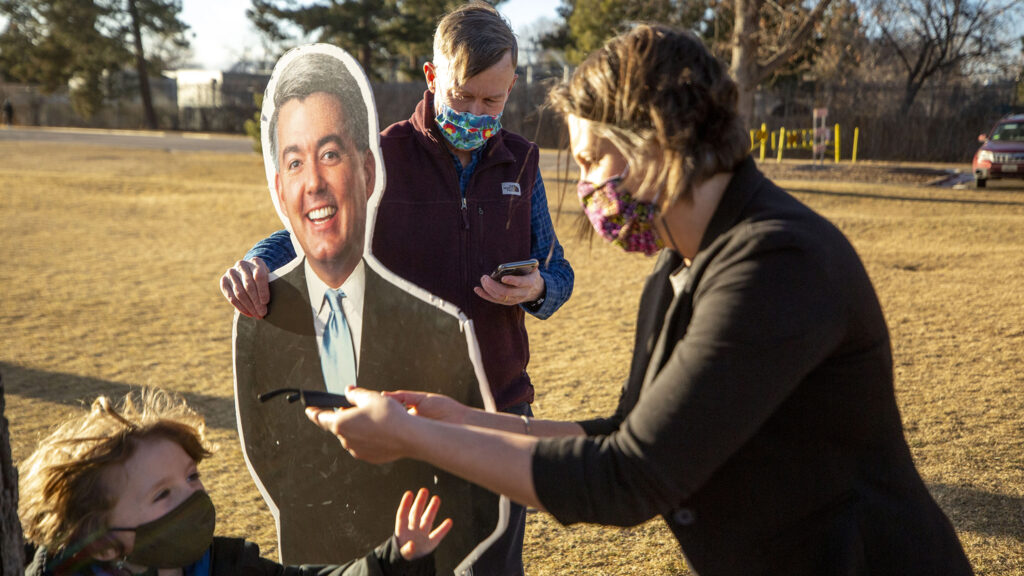 """Katie Farnan meets Sentator John Hickenlooper in City Park to hand off one of the """"Cardboard Cory"""" Gardners that she used for four years to protest Gardner's policies and dearth of public town halls, Jan. 14, 2021."""