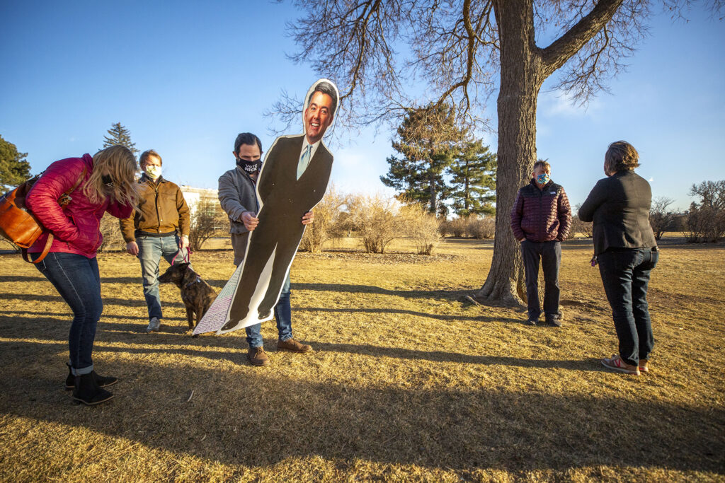 """Katie Farnan (right) meets Sentator John Hickenlooper in City Park to hand off one of the """"Cardboard Cory"""" Gardners that she used for four years to protest Gardner's policies and dearth of public town halls. Jan. 14, 2021."""