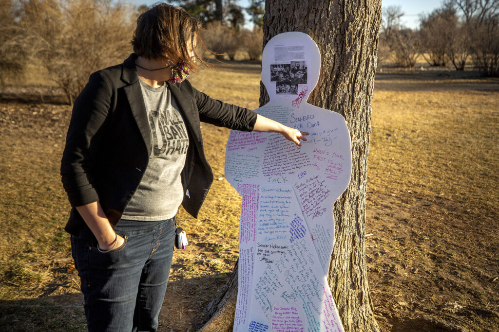 """Katie Farnan points out the messages written to Senator John Hickenlooper on the back of a """"Cardboard Cory"""" Gardner that she used for four years to protest Gardner's policies and dearth of public town halls. Jan. 14, 2021."""
