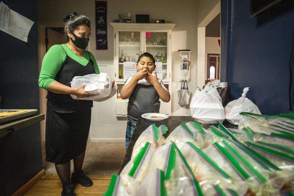 Lucy Castillo watches as Yessenia Martinez's son, Carlos Jr., eats a fresh-made pupusa for breakfast. Jan. 23, 2021.