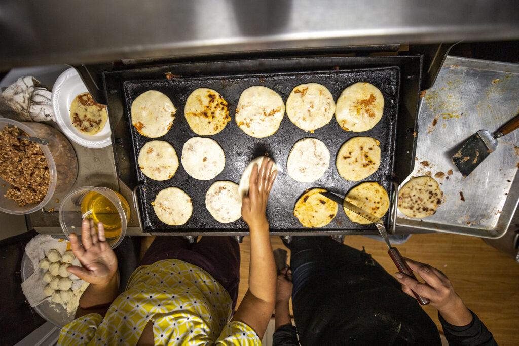 Lupe Urquidez and Yessenia Martinez make pupusas in the kitchen of Martinez's Barnum home. Jan. 23, 2021.