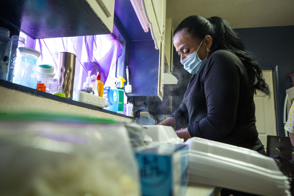 Lupe Urquidez cleans dishware as she helps make pupusas in the kitchen of Yessenia Martinez's Barnum home. Jan. 23, 2021.