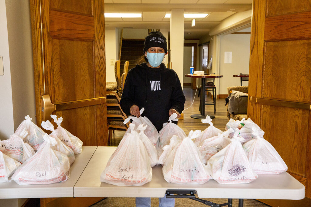 """Jeanette Vizguerra stands with the """"solidarity meals"""" ready for hungry buyers inside the First Unitarian Society of Denver in Capitol Hill. Jan. 23, 2021."""