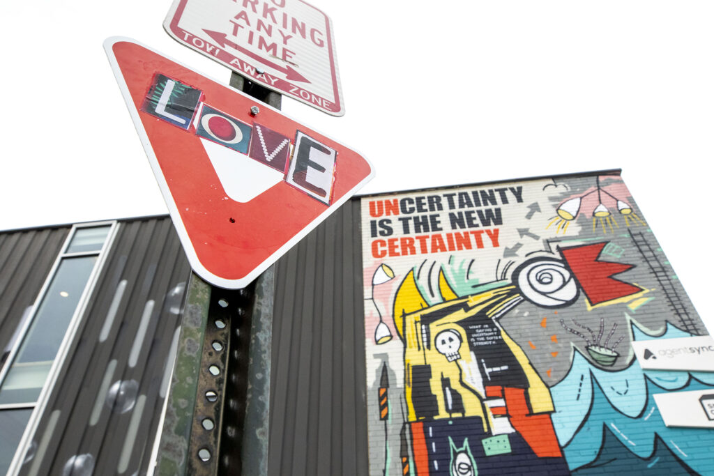 A wheatpasted sign by artist Shannon Galpin is attached to a post next to a mural by Tracy Wiel in Five Point's RiNo art district. Jan. 28, 2021.
