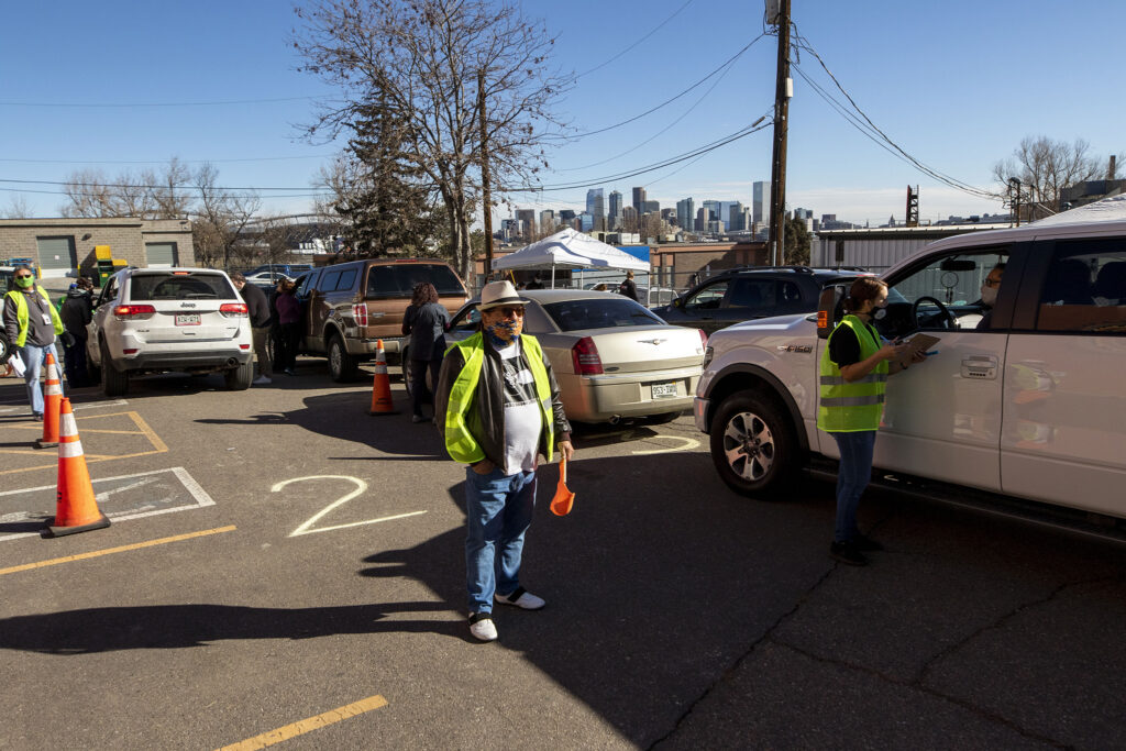 Don Lucero directs traffic in a drive-through COVID-19 vaccine clinic at Servicios De La Raza in Denver's West Colfax neighborhood. Jan. 30, 2021.