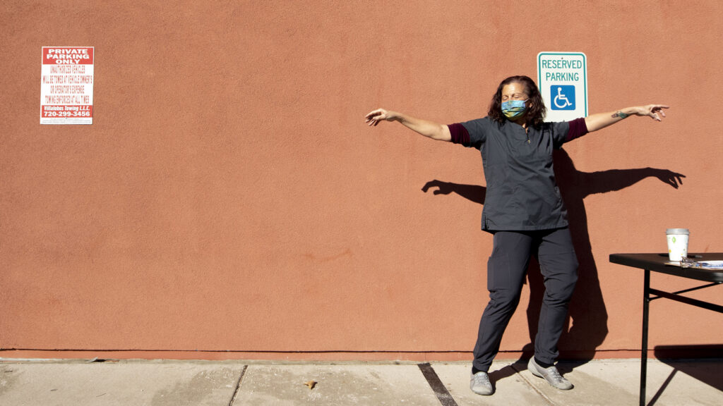 EMT Tina Hortick dances to the music floating over a drive-through COVID-19 vaccine clinic at Servicios De La Raza in Denver's West Colfax neighborhood. Jan. 30, 2021.